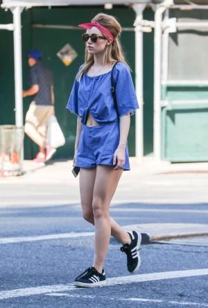 La modelo y actriz Suki Waterhouse por las calles de Nueva York con un mono vaquero con abertura efecto crop top, un recogido cardado y zapatillas Adidas Superstar.